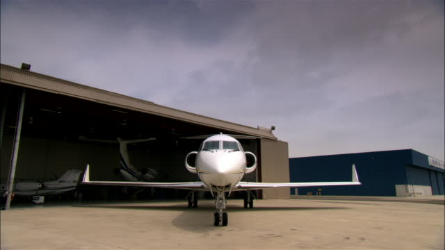 wide shot private jet outside hangar at airport / long beach, california, usa - 飛行機格納庫点の映像素材/bロール