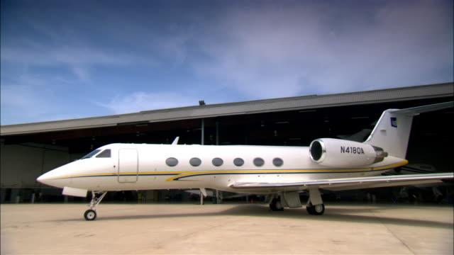Wide shot Private jet outside hangar at airport / Long Beach, California, USA