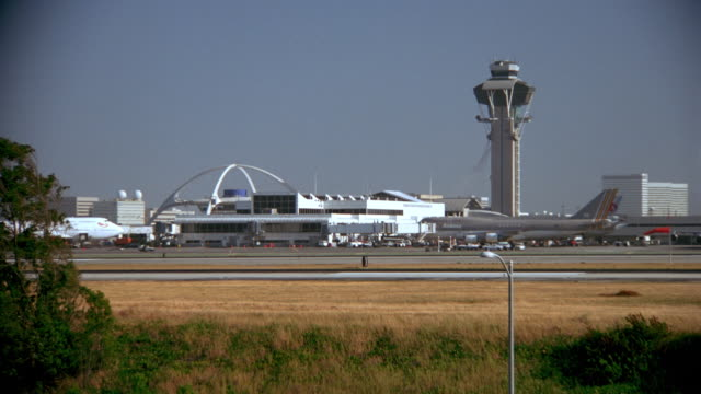 wide shot profile of airplane landing in airport - flughafen kontrollturm stock-videos und b-roll-filmmaterial