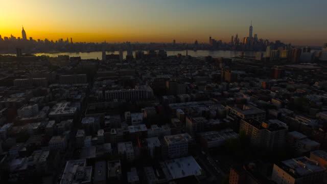 vídeos y material grabado en eventos de stock de wide shot pulling back from nyc skyline over hoboken at sunrise - orange nueva jersey