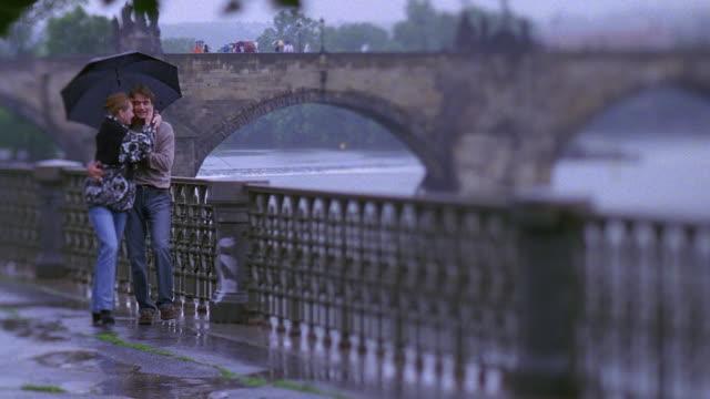 wide shot rack focus couple walking under umbrella in rain, kissing with charles bridge and vltava river background / prague - prague点の映像素材/bロール