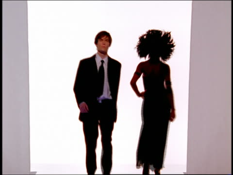 vidéos et rushes de wide shot rack focus male and female models in formalwear walking on catwalk in silhouette + with flashing lights - cadrage aux genoux