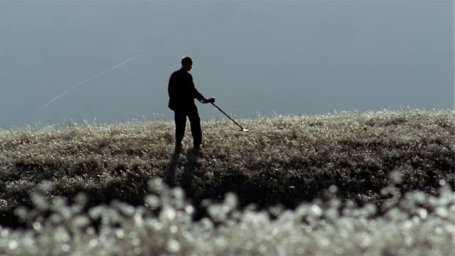 wide shot rack focus pan businessman searching field with metal detector - 金属探知機点の映像素材/bロール