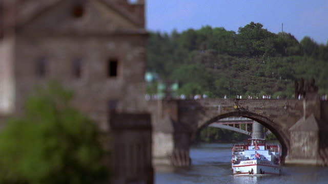wide shot rack focus people cross charles bridge with boat on vltava river and building in foreground / prague, czech republic - vltava river stock videos & royalty-free footage