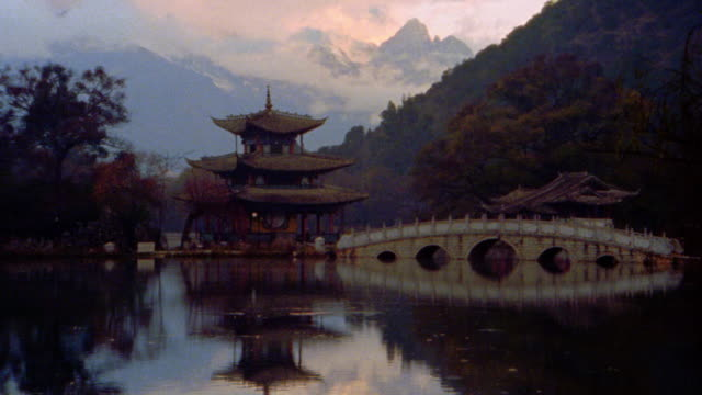 wide shot rain falling on pond, bridge, + traditional chinese pagoda in mountain valley / lijiang, china - pagoda stock videos & royalty-free footage
