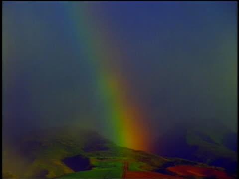 Wide shot rainbow over hills with heavy mist / Hawaii