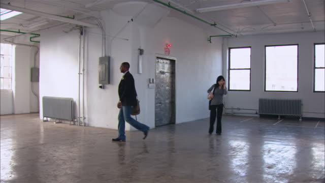 stockvideo's en b-roll-footage met wide shot real estate agent on phone as man looks around empty loft space/ man pointing and walking over to window/ brooklyn, new york - wide shot