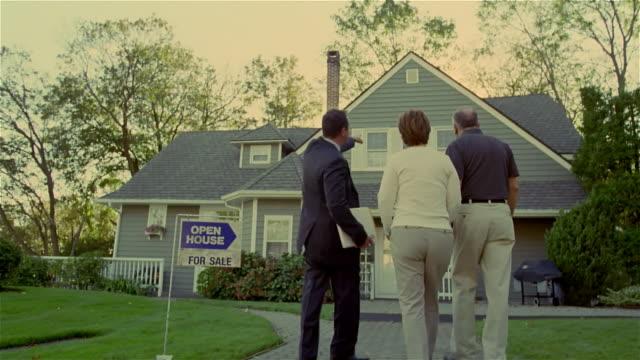 wide shot real estate broker showing house to couple/ solebury, pennsylvania - 不動産の看板点の映像素材/bロール