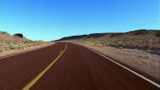 Wide shot rear car point of view driving on curve on rural desert road w/blue sky in background / Nevada