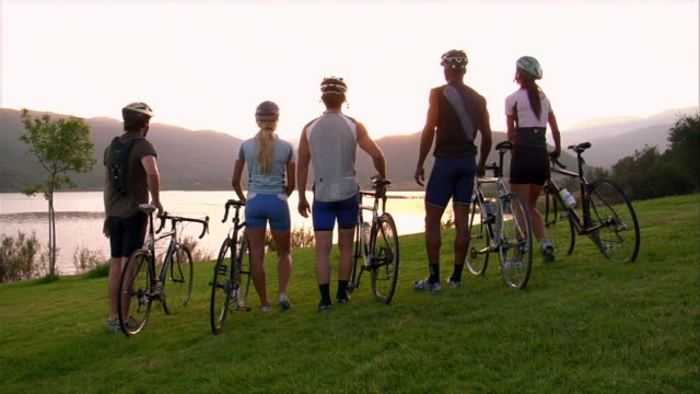 wide shot rear view group of cyclists walking bikes on grass / watching the sun set over a lake / taking off helmets - arm around stock videos & royalty-free footage