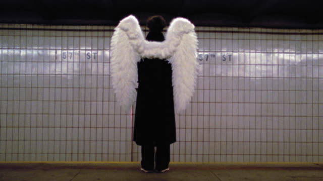 wide shot REAR VIEW man wearing angel wings standing on subway platform with train speeding by / NYC