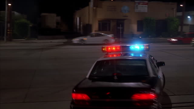 wide shot rear view of police car with siren on turning onto street at night - パトカー点の映像素材/bロール