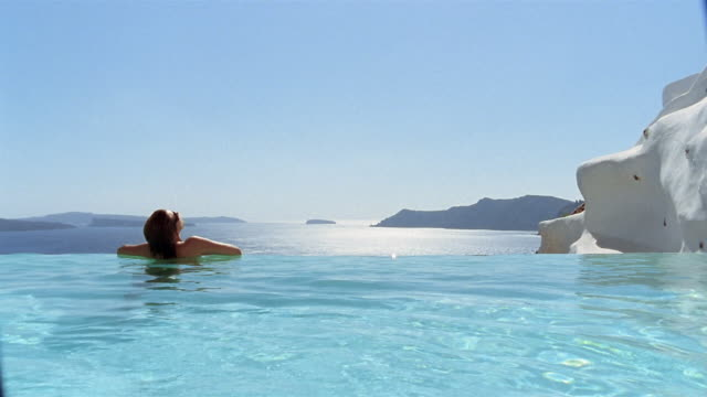 wide shot rear view of woman in infinity pool looking at aegean sea / santorini, greece - infinity pool stock videos & royalty-free footage