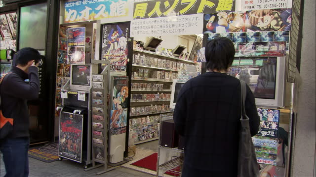 wide shot rear view of young man playing video game in front of game store in akihabara district / tokyo - akihabara stock videos and b-roll footage