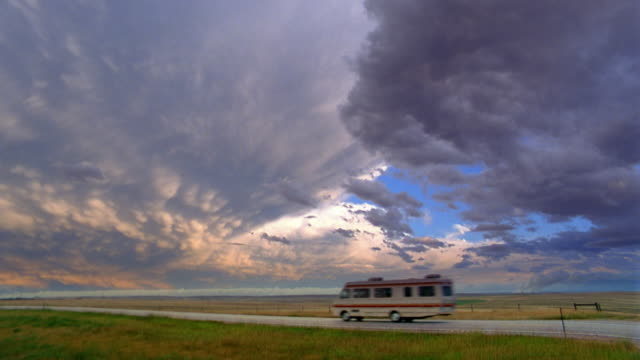 wide shot recreational vehicle driving on rural road w/light and dark clouds in background / nevada - zweispurige strecke stock-videos und b-roll-filmmaterial