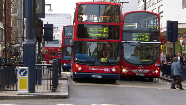 wide shot red double-decker buses pulled up at bus stop / bus leaving bus stop / london - 2005 stock videos & royalty-free footage