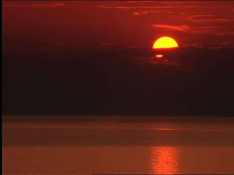 vídeos de stock, filmes e b-roll de wide shot red sunset over ocean / greece - céu romântico