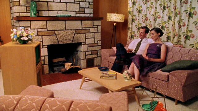 wide shot reenactment couple sitting on sofa and laughing while watching tv in living room - television show stock-videos und b-roll-filmmaterial