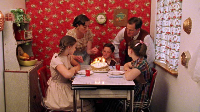 Wide shot REENACTMENT family celebrating boy's birthday at kitchen table with boy blowing out candles on cake