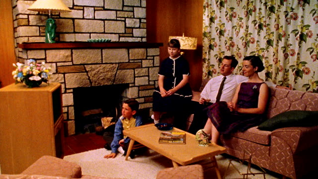 vídeos de stock e filmes b-roll de wide shot reenactment family watching tv in living room - 1950
