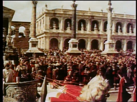 vidéos et rushes de wide shot pan reenactment julius ceaser riding on chariot through crowd in city - reconstitution