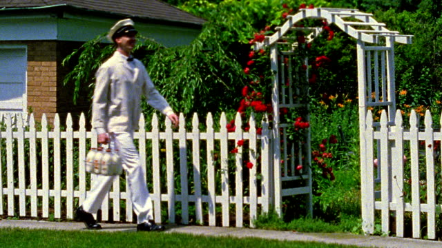Wide shot REENACTMENT milkman walking on street and carrying bottles