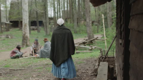 wide shot reenactment of a woman walking toward three men sitting around the fire during the 17th century. - 17th century stock videos & royalty-free footage