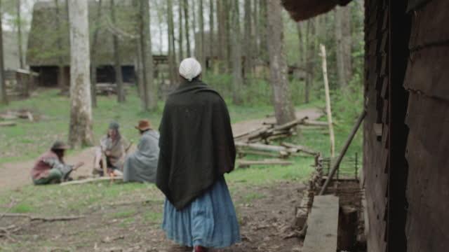 vídeos de stock e filmes b-roll de wide shot reenactment of a woman walking toward three men sitting around the fire during the 17th century. - século xvii
