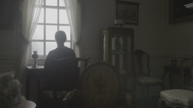 vidéos et rushes de wide shot of an elderly woman getting up from the writing desk and leaving the room - style du xviiième siècle