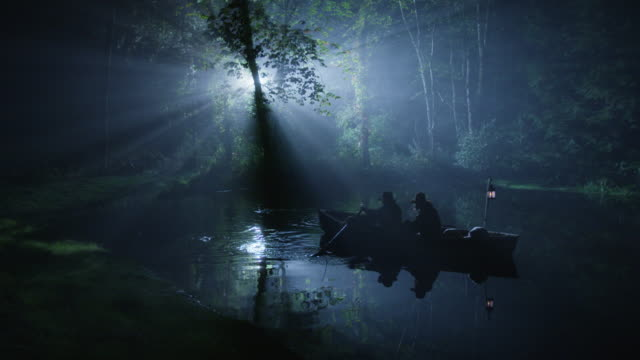 wide shot of men rowing rowboat on a river near the forested riverbank at night - xvii° secolo video stock e b–roll