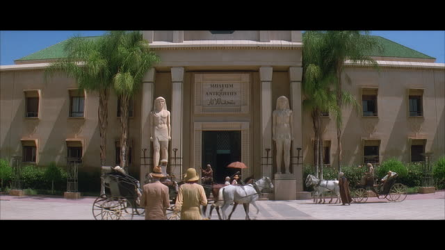 wide shot reenactment pedestrians wearing 1920's dress and walking toward horse carriages and egyptian statues outside entrance of museum of antiquities/ north africa - letterbox stock-videos und b-roll-filmmaterial