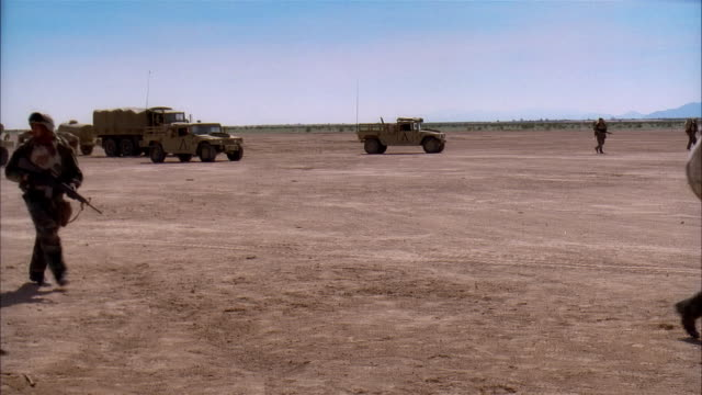 wide shot reenactment soldiers driving military land vehicles and walking across desert battlefield/ mexico - mode of transport stock videos & royalty-free footage