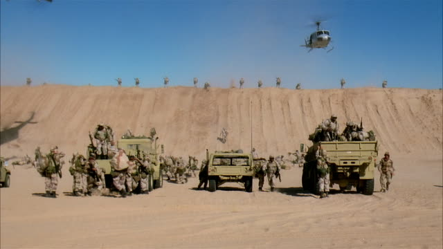 wide shot reenactment soldiers driving military land vehicles over sand dunes and arriving on desert battlefield/ mexico - military helicopter stock videos & royalty-free footage