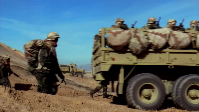 wide shot reenactment soldiers marching with convoy of military land vehicles toward desert battlefield/ mexico - remote location stock videos & royalty-free footage