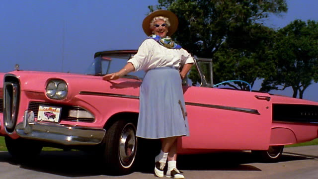 wide shot reenactment woman in poodle skirt posing beside pink 1958 edsel pacer convertible car - collector's car stock videos and b-roll footage