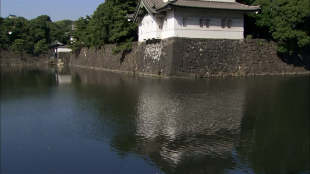wide shot reflection of kokyo in moat at grounds of imperial palace / tilt up to kokyo / tokyo - moat stock videos and b-roll footage