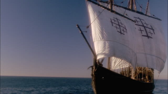 wide shot replica of columbus's ship the nina sailing in ocean / island in background - schiff stock-videos und b-roll-filmmaterial