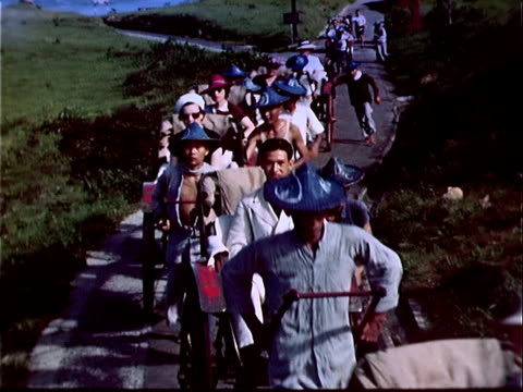 1939 wide shot rickshaw drivers pulling passengers down road/ hong kong - 1939 stock-videos und b-roll-filmmaterial