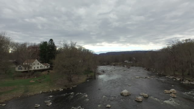 Wide shot rising over rocky river flanked by wintery trees, to reveal long hills on horizon