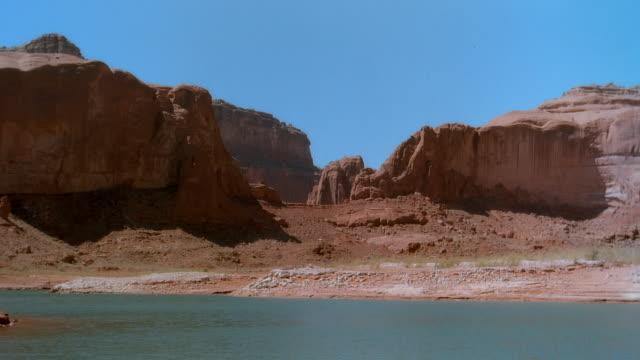 vídeos de stock e filmes b-roll de wide shot river flowing near plateau in lake mead national recreation area/ arizona, usa - tremido