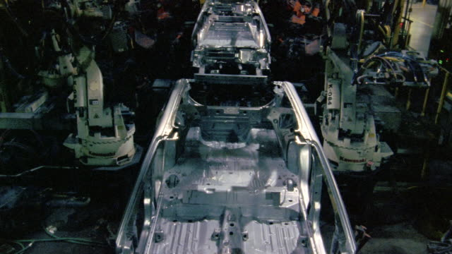 Wide shot robotic arms assembling cars on assembly line in car factory