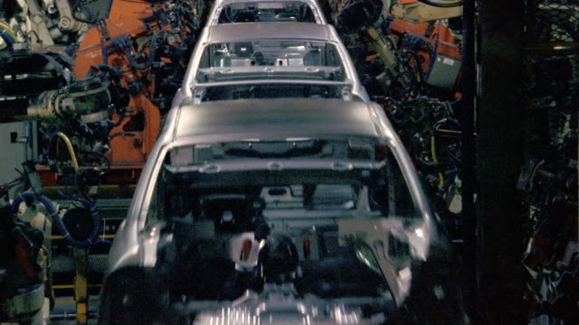 vídeos de stock, filmes e b-roll de wide shot robotic arms welding bodies of cars on assembly line in car factory - indústria