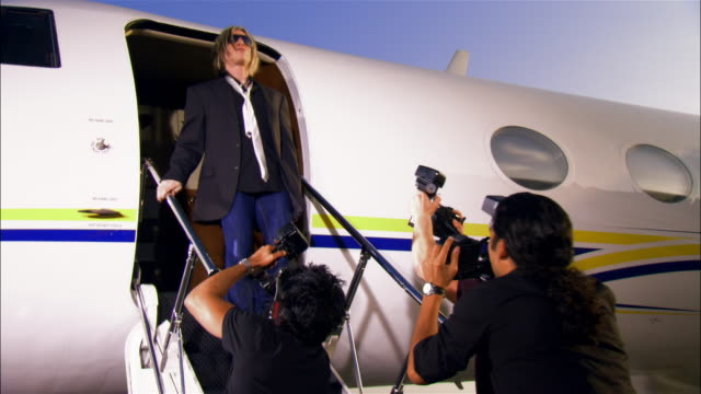 Wide shot Rock star exiting private airplane and walking past paparazzi photographers / Long Beach, California, USA