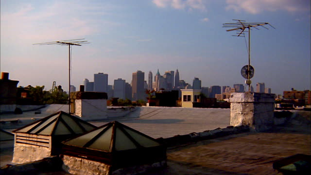wide shot rooftop view of manhattan skyline w/antennas in foreground / nyc - television aerial stock videos and b-roll footage