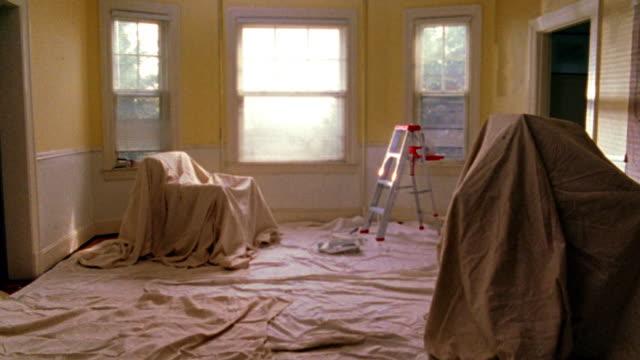 vídeos de stock e filmes b-roll de wide shot pan room with windows, drop cloths, + stepladder - pano de protecção