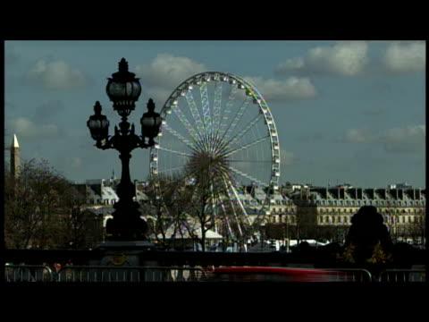 2000 Wide shot Roue de Paris, the giant ferris wheel, turning near street light/ Paris, France