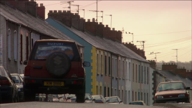 wide shot row houses on street / rear view of suzuki 4x4 driving down street / derry, northern ireland - northern ireland stock videos & royalty-free footage