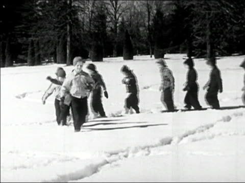 1945 Wide shot row of children marching through snow/ AUDIO