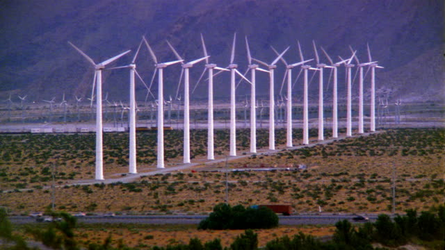 wide shot row of wind turbines spinning amidst busy freeway and railway line at foot of mountain / palm springs, california - trucks in a row stock videos & royalty-free footage