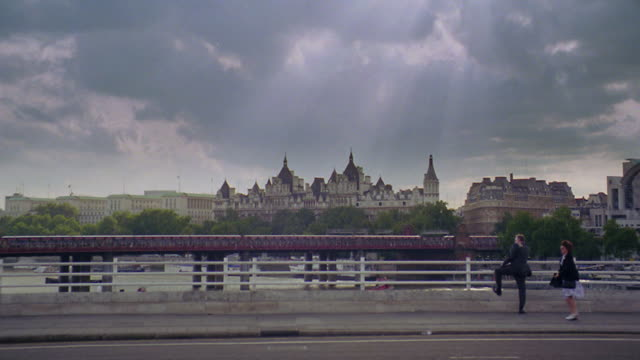 wide shot royal courts of justice with people standing on bridge in foreground / london, england - royal courts of justice stock videos & royalty-free footage